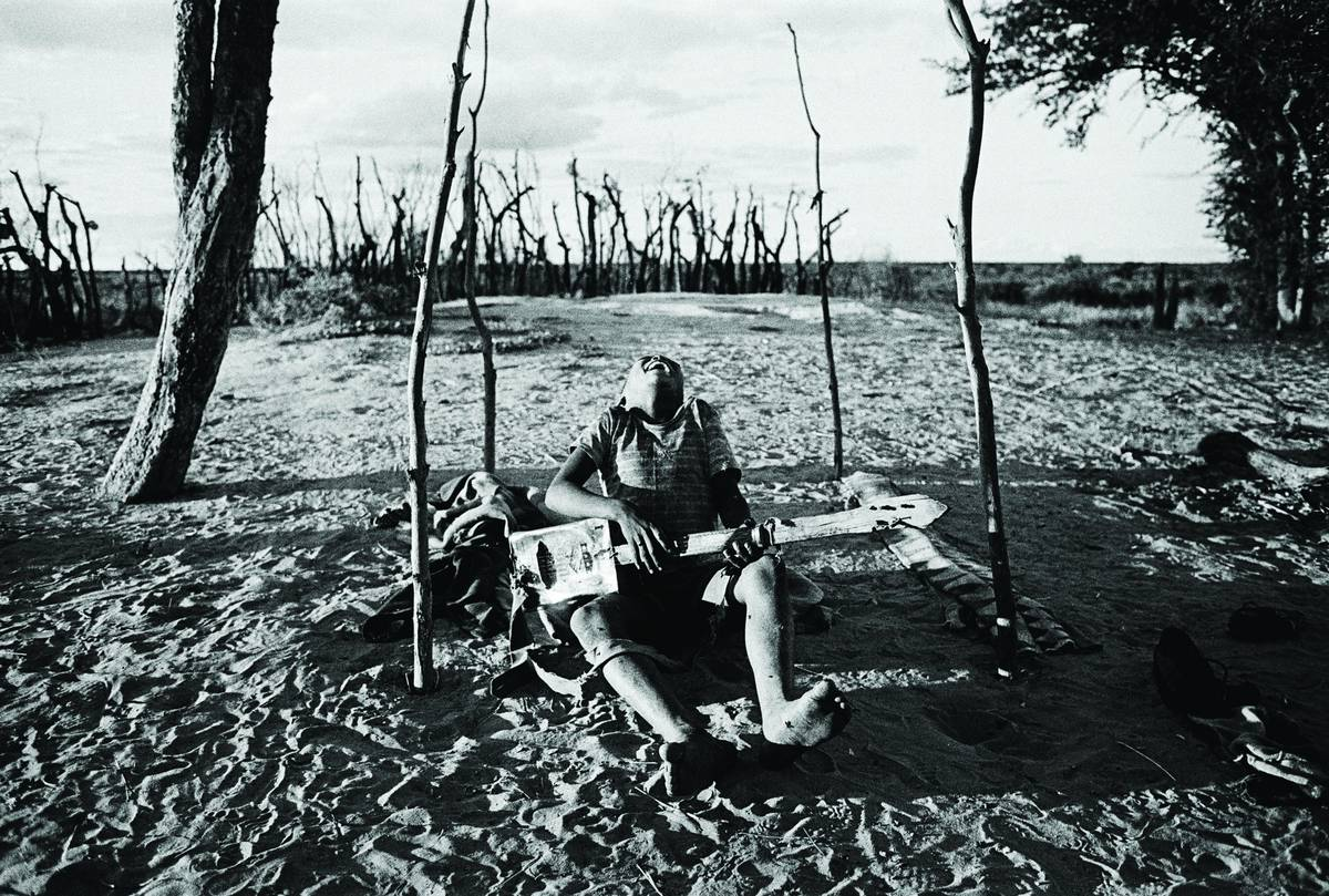 Boy playing a homemade guitar. Bushmanland, Namibia, 1987.