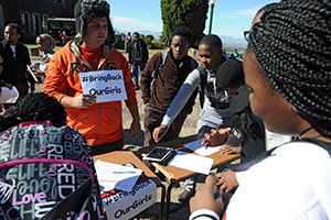 Taking action: Roscoe Jacobs, wearing orange, holds up a placard demanding the return of school girls that were kidnapped in Nigeria in April, while students sign a petition urging the South African government to step in.