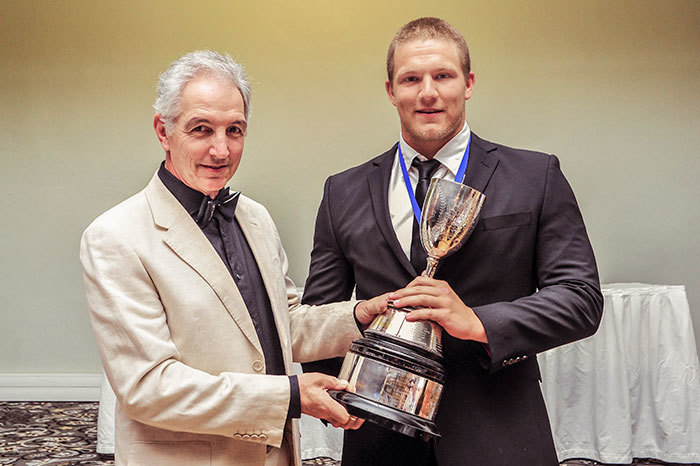 Vice-Chancellor Dr Max Price hands the Jamison Trophy to UCT's top athlete for 2014, water polo star Devon Card.
