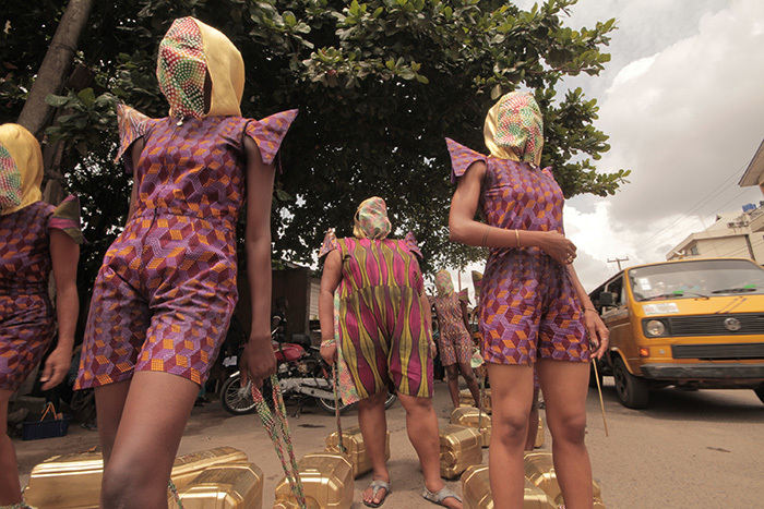KWuru-Natasha's <i>Can't I just decide to fly?</i> is a public endurance performance, in which a group of masked women haul water kegs through the streets of Cape Town, exploring the relationship between physical labour, beauty and social change.</i>