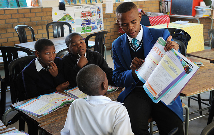 A Grade 11 student from the Centre of Science and Technology (COSAT) in Khayelitsha helps Grade 6 learners from Intshayelelo Primary during the homework club established to help the younger learners improve among others their systemic test results.