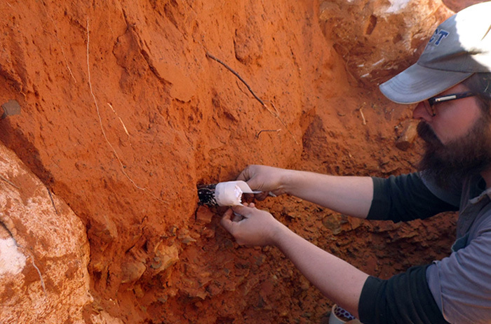 Mr Steven James Walker from the Department of Archaeology at UCT extracts a sample at the interface between the overlying red sands and the Earlier Stone Age archaeological deposits at the Kathu Townlands site. (Photo by Vasa Lukich)