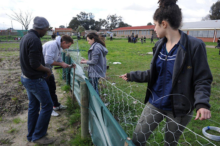 All out for Madiba: UCT students at the Walter Teka Primary School in Nyanga, where they put up a garden fence, painted toilet walls and played sports with the school's students as part of their Mandela Day 2013 contribution.