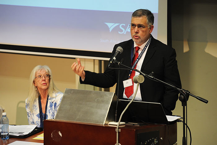 Dr Beric Croome from law firm Edward Nathan Sonnenbergs addresses attendees at the <i>Income Tax in South Africa: The first 100 years</i> conference, with Prof Jennifer Roeleveld, a conference organiser, looking on.
