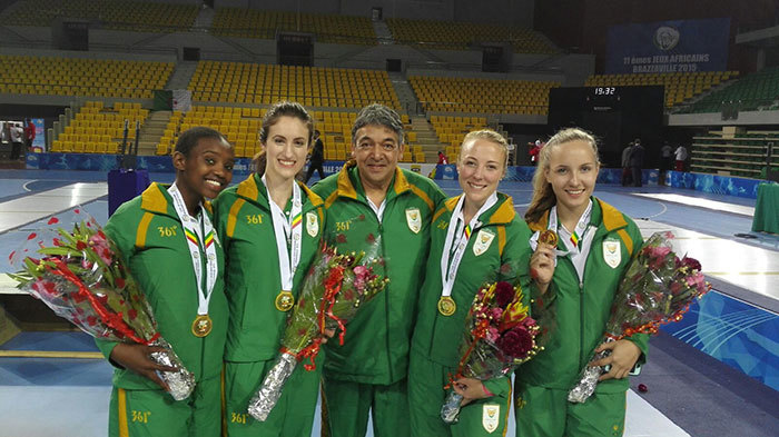 The women's epee fencing team (in green tracksuits) celebrate their gold medal at the African Games. Aphiwe Tuku, Giselle Vicatos (UCT Masters student), Randall Daniels (Manager), Tamryn Carfoot and Juliana Barrett. Photo supplied.