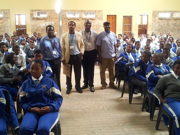 Standing between rows of seated Fezeka High learners (from left): Associate Professors Collet Dandara, Ambroise Wonkam, Ikechi Okpechi, and Dr Esau Ticha Muluh.