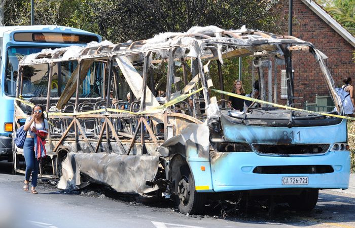 Violence must fall: The skeleton of a Jammie Shuttle, torched during Tuesday night's campaign of vandalism and intimidation.