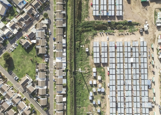"This picture of unequal living conditions taken near Strand in the Cape Town metropolitan area by UCT alumnus Johnny Miller is <a href=""/dailynews/?id=9750"" style=""font-weight: normal;"">a stark illustration of the social challenges facing South Africa</a>."