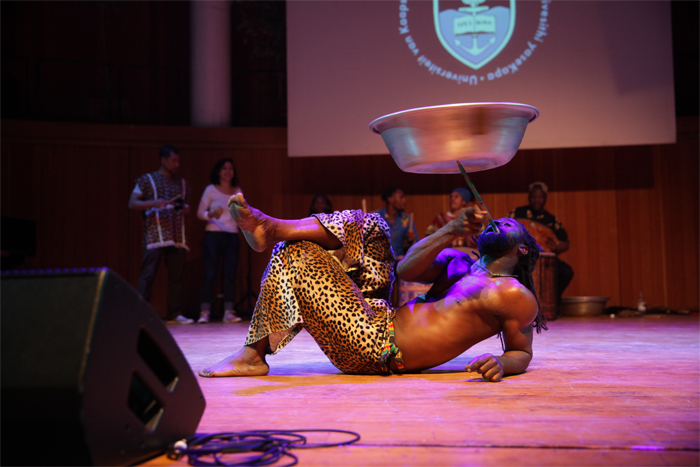 Guest Kofi Lartey performed a fire dance, which adapts contemporary fire-dancing techniques to popular kpanlogo rhythms of Ghana. Lartey is a Ghanaian master drummer and dancer who has contributed much to the College of Music's programme in recent months. Here he controls a spinning bowl while executing an acrobatic dance.