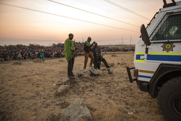 Lonmin employees gather at the base of a hill called Wonderkop at Marikana, outside Rustenburg in the North West Province of South Africa, 15 August 2012. The miners were calling for the minimum wage to be raised from R4 000 a month to R12 500.