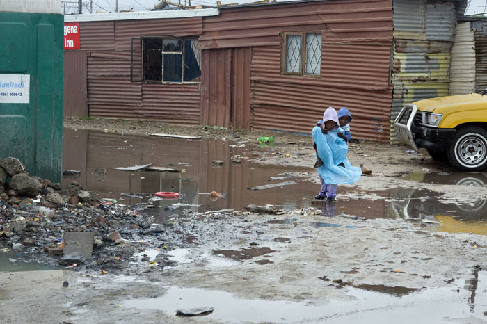 A child walks through a flooded informal settlement.