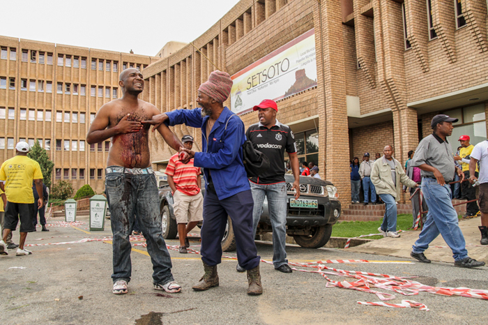 Andries Tatane – who joined some 4 000 Ficksburg residents on 13 April 2011 to protest poor service delivery in the area – clutches his chest after police shot him with rubber bullets; he collapsed and died 20 minutes later.