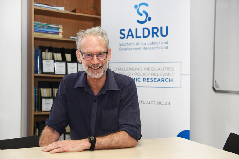 Director of the Southern Africa Labour and Development Research Unit (SALDRU), Prof Murray Leibbrandt, with the new SALDRU logo in the background. <b>Photo</b> Robyn Walker.