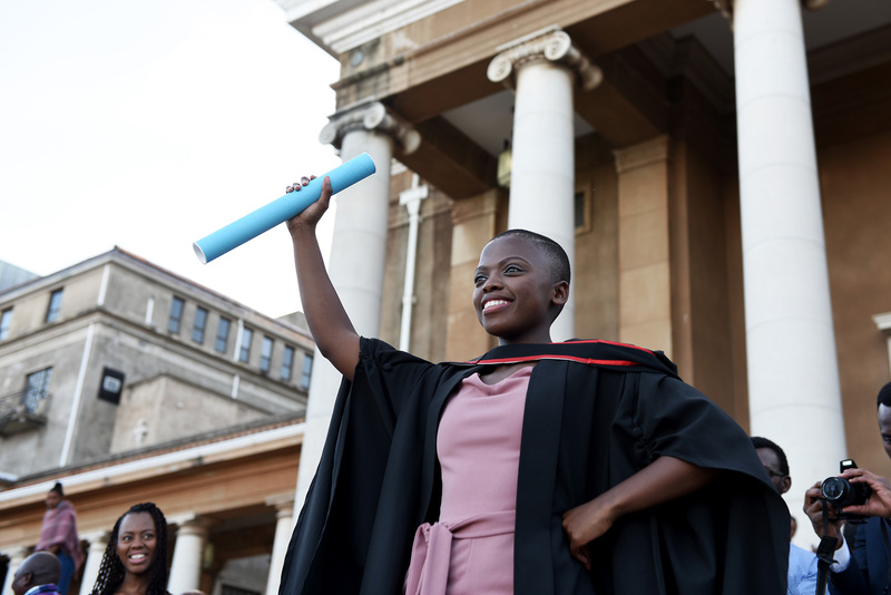 A UCT graduate poses outside Memorial Hall after receiving their degree.