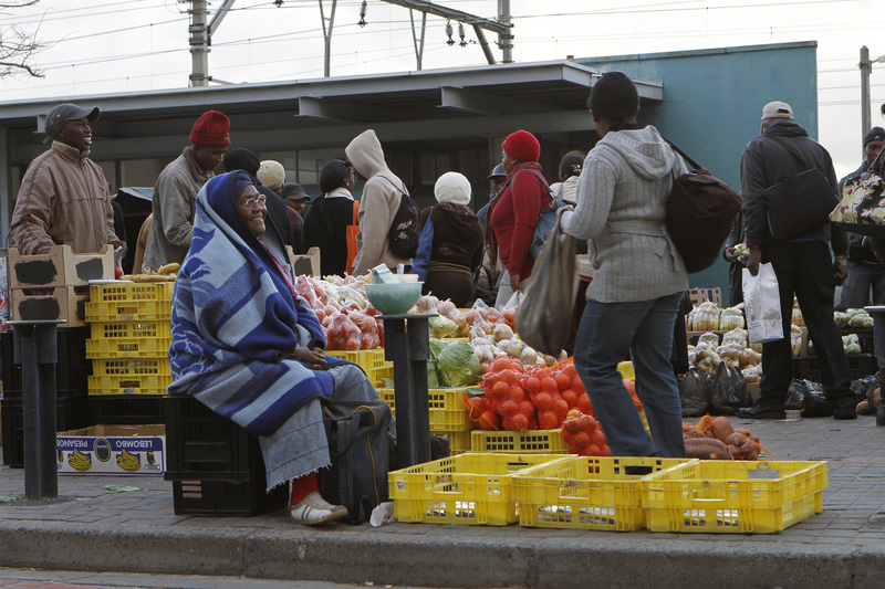 Commuters approach the Wynberg taxi rank in Cape Town on their way home. Informal traders capitalise on the passing trade.