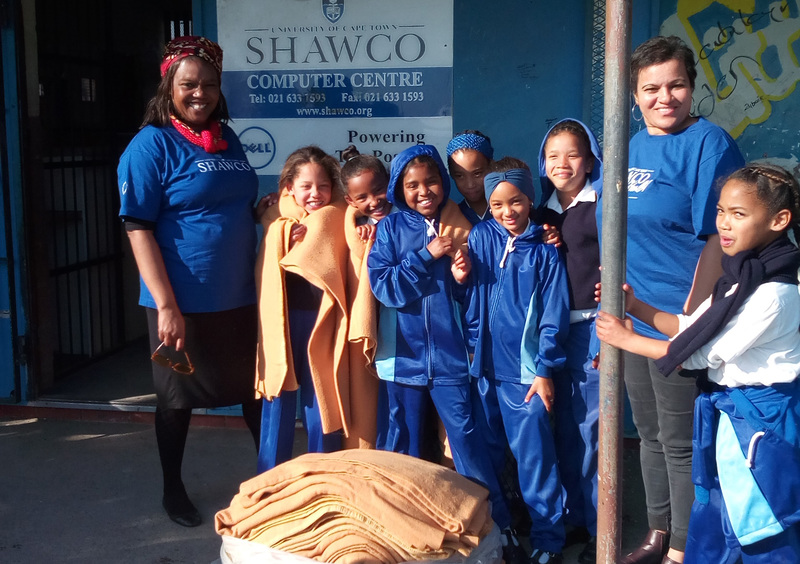 SHAWCO office administrator Thembisa Nkwaba and house keeper of SHAWCO House Belinda Martin with some of the learners who have benefitted from SHAWCO's winter-warmth drive on Mandela Day.