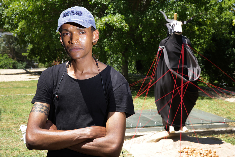Final-year law student Kneo Mokgopa with the installation, which comprises a mannequin draped in black fabric with a cardboard bull's head, tethered to the ground with a network of red ropes and approached via a path strewn with eggshells.