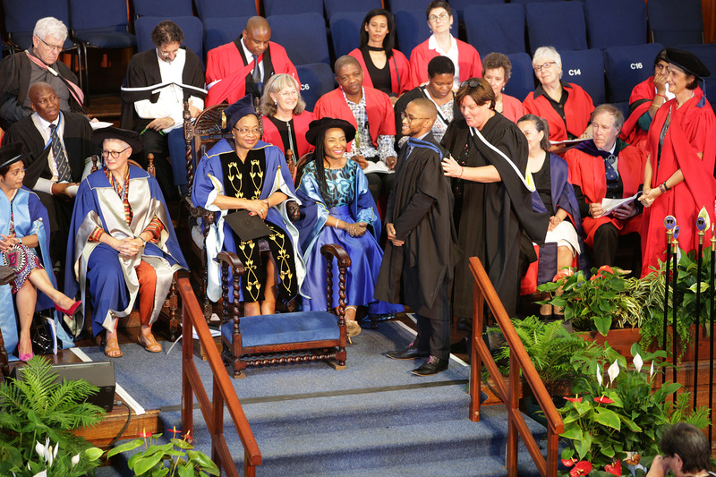 Gerda Kruger, Executive Director: Communication and Marketing Department, hoods her son Siya Kruger at the Humanities graduation event, as Chancellor Graça Machel and VC Prof Mamokgethi Phakeng look on.
