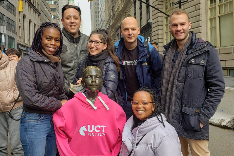 AIFMRM MPhil in Financial Technology students in New York, co-opting the bronze statue, Fearless Girl, into their class. In the picture are (from left) Masego Modibane, Aidan Fourie, Ashleigh Favish, Assoc Prof Co-Pierre Georg, Kungela Mzuku, and Ryan Jacobson.