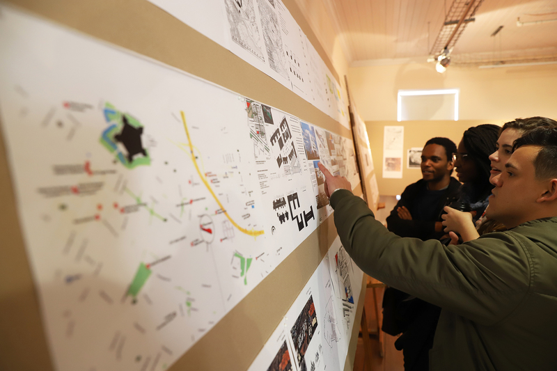 Students study the pop-up exhibition of past architecture honours students' work that was displayed at the District Six Museum Homecoming Centre.