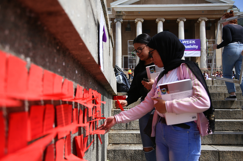 Students interact with the installation which allowed viewers to share their personal interpretations of how GBV impacts the UCT community, writing comments on rectangles of red paper placed along the steps leading up to the Plaza.