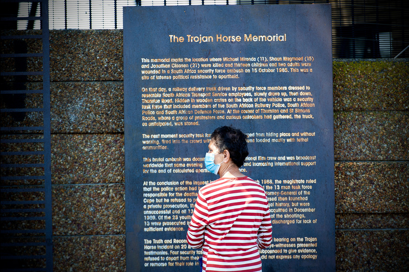 A passer-by engages with the storyboard at the Trojan Horse Massacre memorial, which is located in Thornton Road in Athlone, Cape Town.
