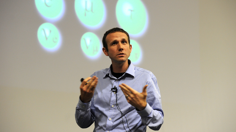 Basis of being: Dr Andrew Hamilton, pictured here at a 2012 public lecture about the possible sighting of the Higgs boson particle, was awarded a P-rating for his continuing insights into the understanding the Universe at its most fundamental level.