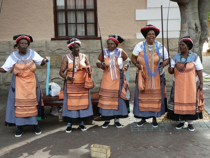 Five Xhosa women performing in traditional AmaXhosa costumes and face paintings at the Waterfront in Cape Town. Chell Hill / Commons Wikimedia.