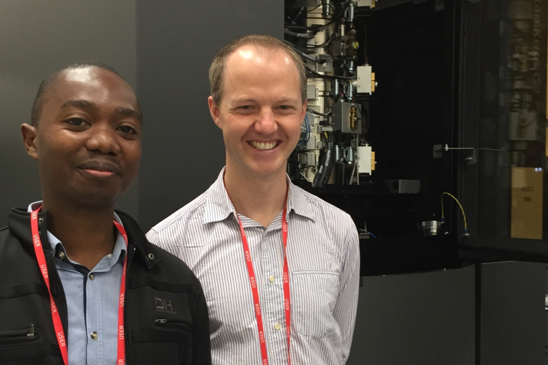 UCT researchers Dr Andani Mulelu and Dr Jeremy Woodward stand next to the super-microscope they used to make their biochemistry breakthrough at the Electron Bioimaging Centre at Diamond Light Source in the United Kingdom. <b>Photo</b>&nbsp;Adriana Klyszejko.