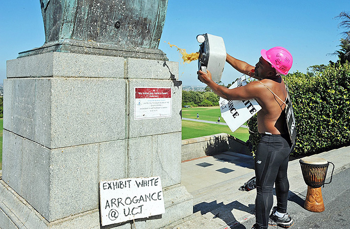 On 9 March 2015, fourth-year political science student Chumani Maxwele throws what appears to be human excrement at the statue of Cecil John Rhodes on the campus rugby field, saying that many black students are offended by the colonial atmosphere at UCT. Photo by David Ritchie, <em>Cape Argus</em>.