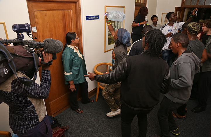 Students protesting outside the registrar's office on 23 March, with Dr Moonira Khan, director of UCT's Department of Student Affairs, in the doorway. Photo by Je'nine May.