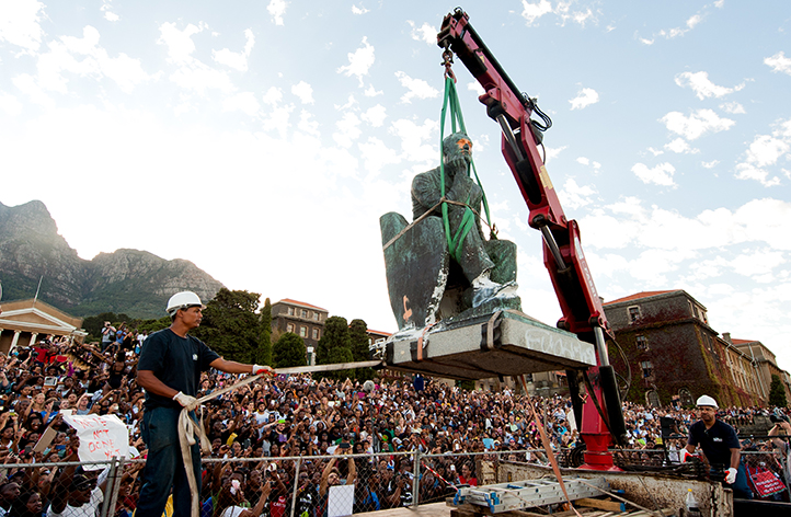 The roar of the crane's starter motor is drowned out by the roar of the crowd when they realise that the time for the removal of Rhodes' statue had arrived. Photo by Roger Sedres.