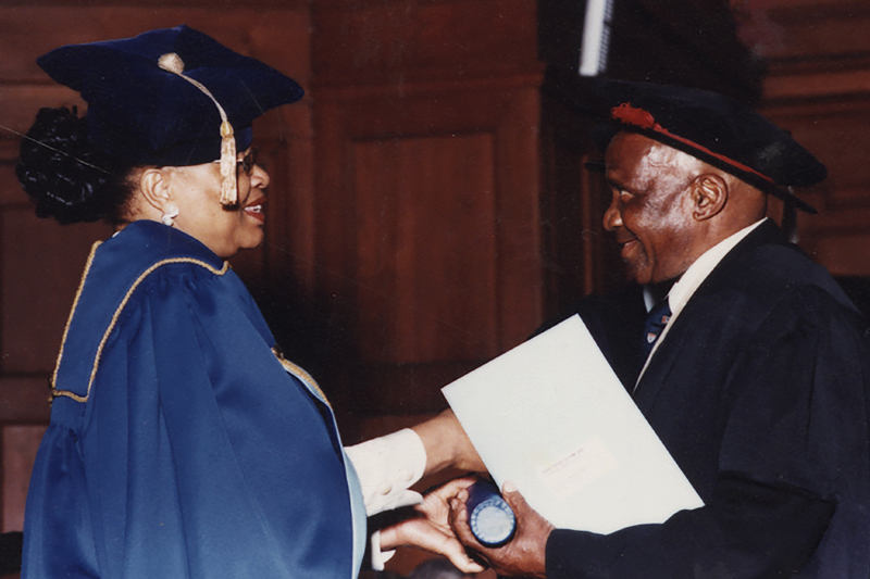 Hamilton Naki receives his honorary MSc in medicine from  UCT Chancellor Graça Machel in 2003. Naki was an informally taught surgical technician at Groote Schuur Hospital where he  started working as a gardener and cleaner before becoming the hospital's principal lab technician. He eventually helped to teach over 3 000 surgeons, and assisted with Chris Barnard's organ transplant programme.