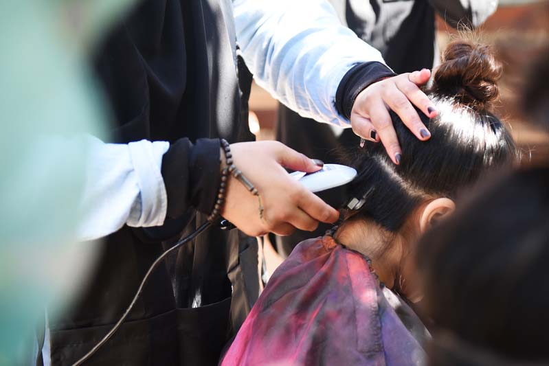 A student gets the underside of her hair cut and shaved.