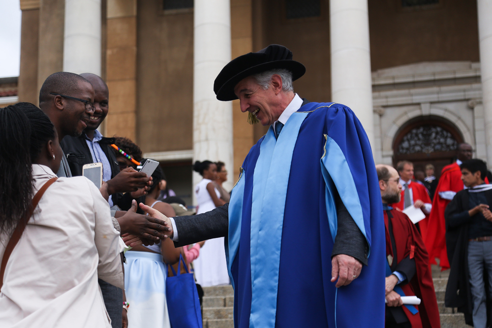 Vice-Chancellor Dr Max Price shakes hands with a student after their graduation ceremony.