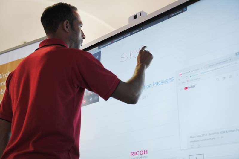 A Ricoh exhibitor demonstrates some of the capabilities of the Ricoh interactive whiteboards.