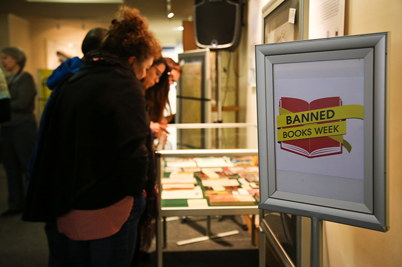 Guests at the exhibition examine some of the previously banned books that are on display