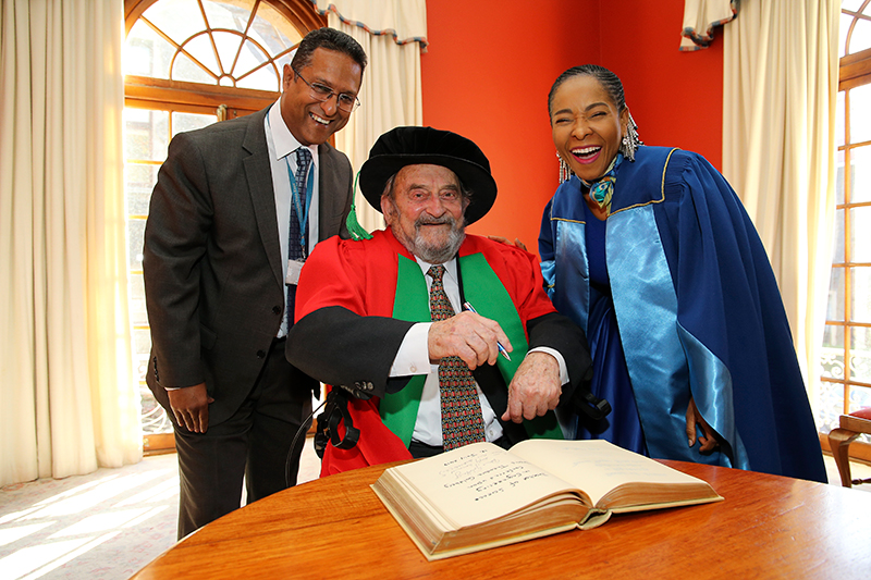Honorary doctorate recipient Denis Goldberg and VC Prof Mamokgethi Phakeng share a light moment with Registrar Royston Pillay during the signing of the book of honour.