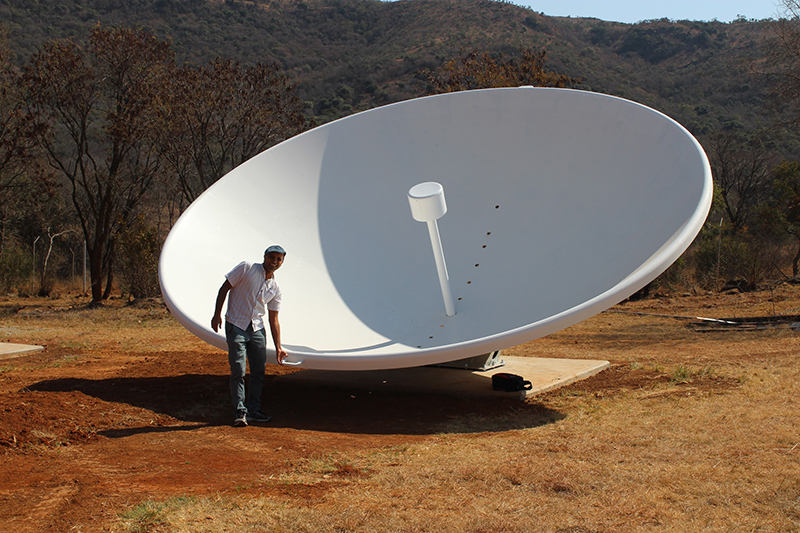 Kavilan Moodley, professor at the University of KwaZulu-Natal and principal investigator of HIRAX, alongside one of the newly installed prototype dishes.