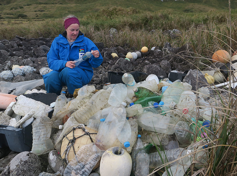 Co-author of the study Dr Maëlle Connan scores bottles washed ashore on the west coast of Inaccessible Island.